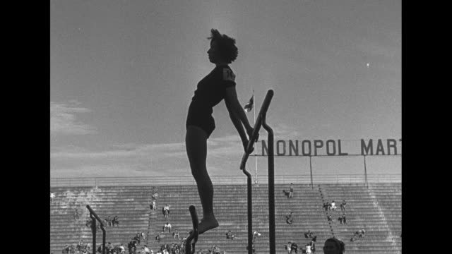 looking down on female gymnast performing on uneven bars / gymnast on bars / man holding cigarette sitting beside a woman in stands / woman with... - doing the splits stock videos & royalty-free footage
