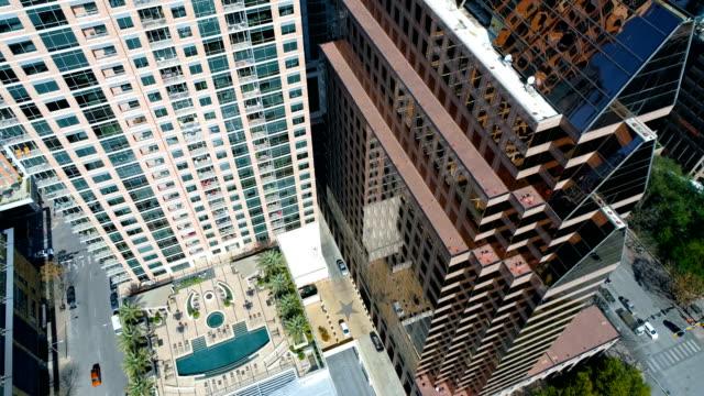 vídeos de stock, filmes e b-roll de olhando para baixo em hotéis e altos arranha-céus modernos skyline de pátio e piscina deck - pátio