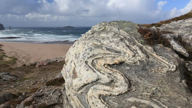 looking down on sandwood bay towards the sea stack, am buachaille, with lewisian gneiss rock in the foreground. lewisian gneiss is some of the oldest rock on the planet. - stack rock stock videos and b-roll footage