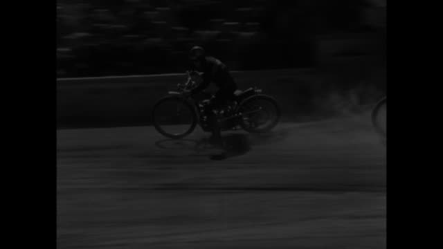 looking down on section of racetrack and stands at winter sports stadium in bavaria as motorcycle race starts narration in german / crowd in stands... - 1947 stock-videos und b-roll-filmmaterial