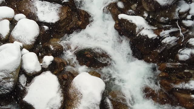 looking down on slow motion snow falling on a waterfall then tilt up - snowing stock videos & royalty-free footage
