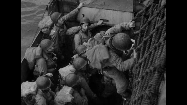 ms looking down on soldiers gathered on deck of ship climbing over the side on way into amphibious landing craft / ms soldier climbing down netting... - major league soccer stock videos and b-roll footage