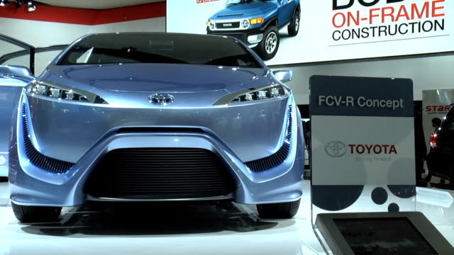 WS HA looking down on Toyota revolving on turntable / CU door graphics down near rocker panel / WS front end of car and info sign / CU 'Fuel Cell'...