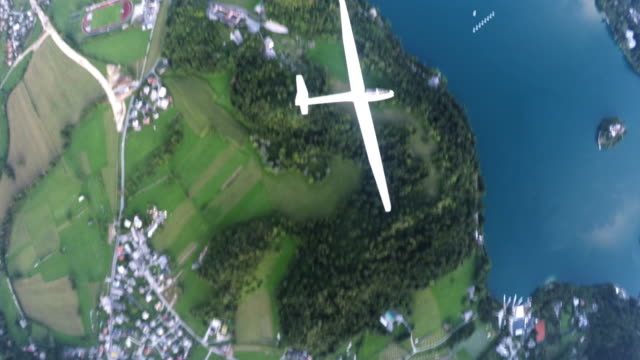 looking down onto a glider plane sailing above a lake - glider stock videos & royalty-free footage