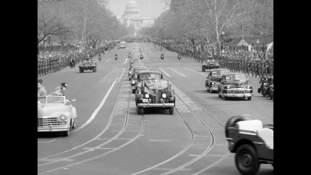 Looking down Pennsylvania Avenue with US Capitol in bg as parade moves toward camera police on motorcycles truck with photographers making turn...