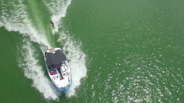 epic looking down to up reveal wake surfing - drone aerial video 4k wakeboard, wake surfing and wake skating on georgia lake on beautiful water extreme action sports, front flip, backflip, twist and wipeout tracking reveal 4k sports - epic film stock videos & royalty-free footage