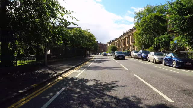 looking forward from a car as it turns a corner in a historic glasgow neighborhood of victorian townhomes, with lush trees, people walking on the sidewalk, and a bright blue sky - high street stock videos & royalty-free footage