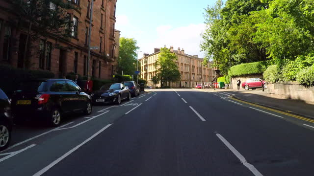 looking forward from a car down a street as it turns a corner in a historic glasgow neighborhood of victorian townhomes, with lush trees, people walking on the sidewalk, and a bright blue sky - corner stock videos & royalty-free footage