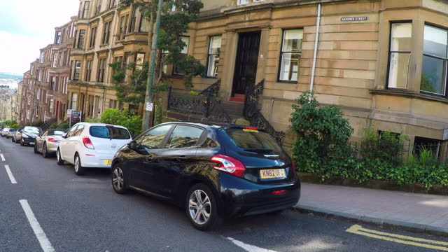 looking forward from a car down a street as it turns a corner in a historic glasgow neighborhood of victorian townhomes, with lush trees, and a bright blue sky - corner stock videos & royalty-free footage