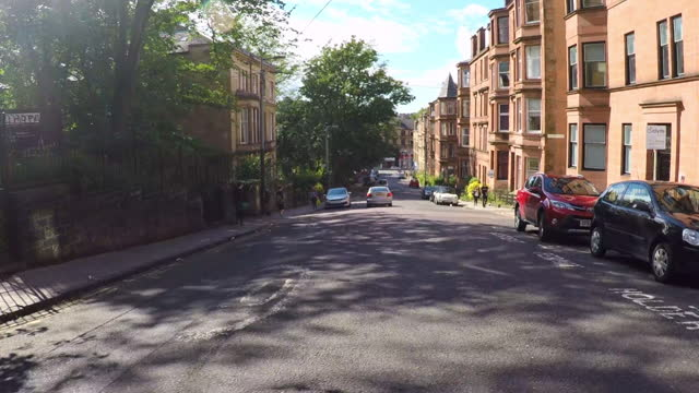 looking from a car down a street as it turns a corner in a historic glasgow neighborhood of victorian townhomes, with lush trees, people walking on the sidewalk, and a bright blue sky - stationary stock videos & royalty-free footage