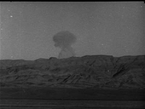 sheep mountain range w/ mushroom cloud bg, brief cloud behind mountains. note: many scratches. nye county, nevada test site, nts, desert, atomic,... - 1952 stock-videos und b-roll-filmmaterial