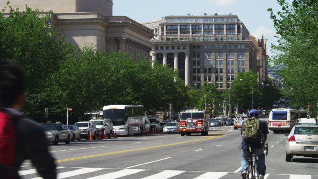 vídeos de stock e filmes b-roll de looking north up 7th street from madison drive in washington dc, national archives at left; fire truck goes by. shot in may 2012. - carro de bombeiro