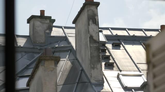 vidéos et rushes de looking out a window at rooftops in an apartment building in paris, france, europe. - slow motion - destination de voyage