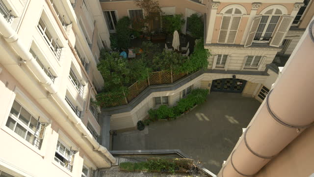 looking out a window in an apartment building courtyard in paris, france, europe. - slow motion - atrium grundstück stock-videos und b-roll-filmmaterial