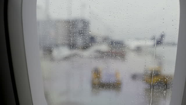 looking out of a plane window onto the airport on a rainy day - looking through window stock videos & royalty-free footage