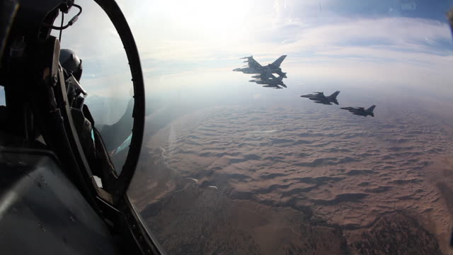 POV Looking out of F-16 fighter jet cockpit onto F-16 fighter jets flying in formation over the Great Sand Dunes National Park, Colorado, USA