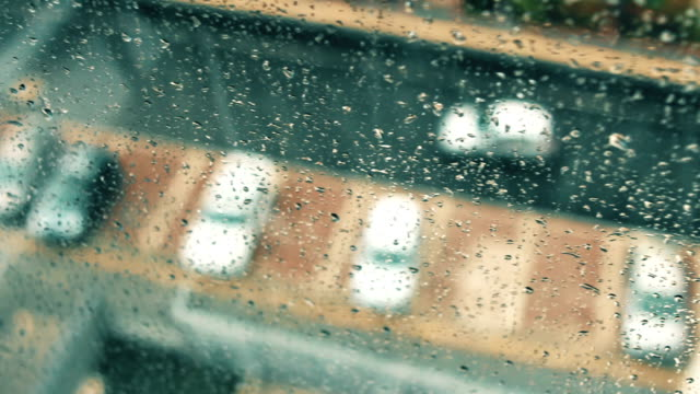 Looking out of window glass with raindrops to the parking lot in a rainy day