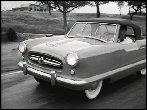 vídeos de stock, filmes e b-roll de pov looking out windshield of nash metropolitan as garage door goes up to reveal the outside car drives out driver turns on windshield wipers / ws... - plano americano