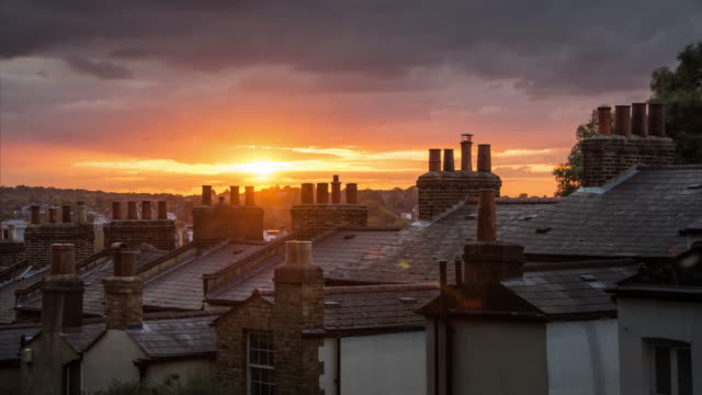 looking over chimneys and slate roofs of residential homes towards the setting sun as it passes through low darkening clouds in south london - chimney stock videos & royalty-free footage