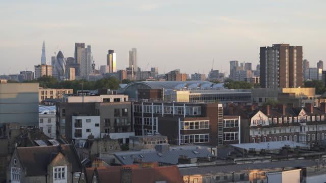 looking over london rooftops, at dusk. towards the city skyline. - イーストロンドン点の映像素材/bロール