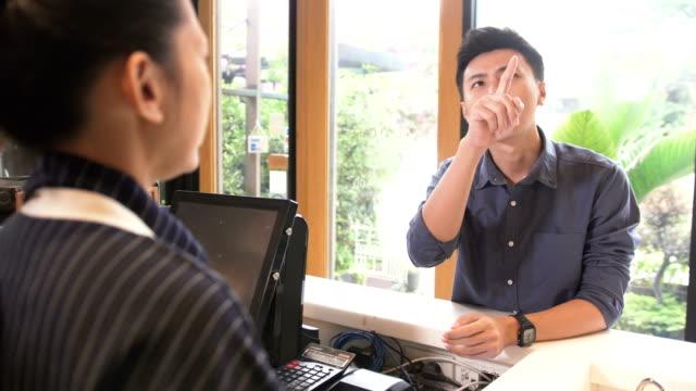 カフェでコーヒーを注文するメニューにアジア barista:male 顧客の中点の肩越しに見ています。 - 注文する点の映像素材/bロール