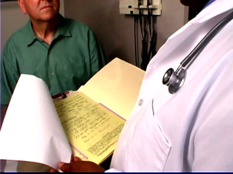 looking over the doctor's shoulder at the patient's file tilting up to them talking during an exam. - only mature men stock videos & royalty-free footage