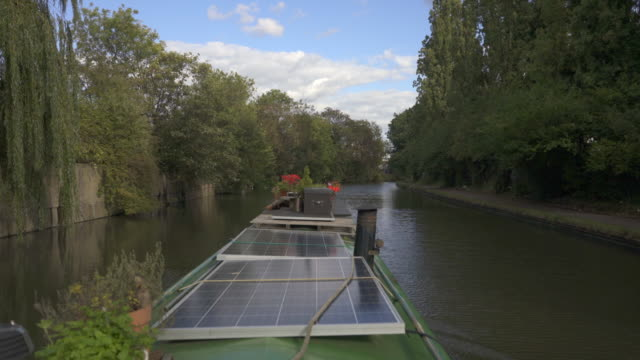 Looking over the top off a narrow boat with solar panels.