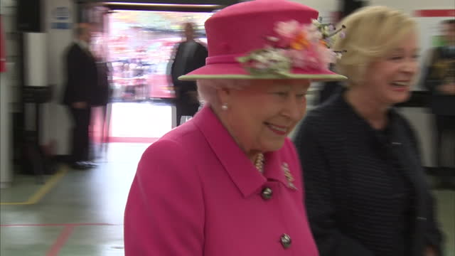 Looking radiant in bright pink Queen Elizabeth II met with Royal Mail staff at a Windsor delivery office Husband Prince Philip Duke of Edinburgh...