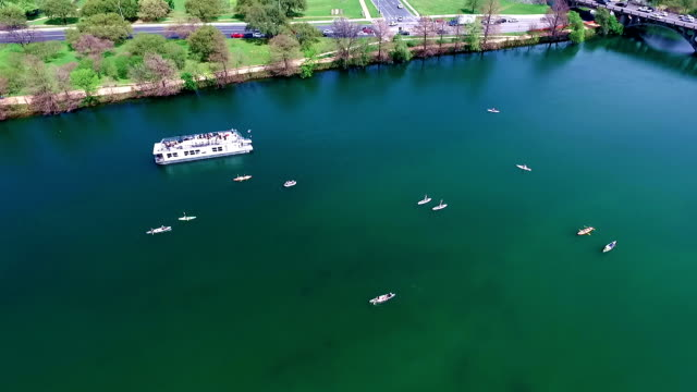 looking straight down at kayakers moving fast. Flying over the Middle of Lake Aerial View Austin Texas Colorado River Fun Spring water activities with kayakers and Party Boat during SXSW Spring Break 2016