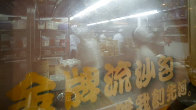 looking through a window to see traditional chinese rice and dim sum steamers being prepared in a busy restaurant kitchen, central, hong kong, china - model and property released -, time-lapse - chinese food stock videos & royalty-free footage