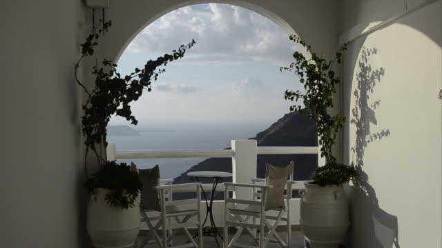 MS Looking through archway at ocean with steep slope on mountain / Fira, Santorini, Greece