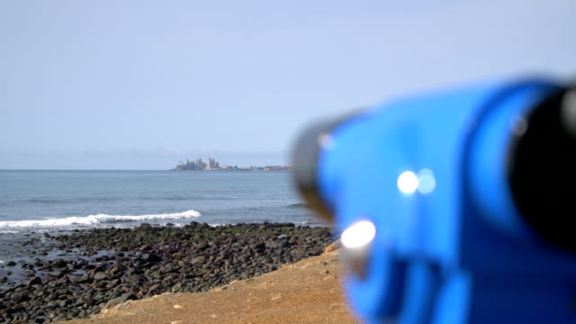 Looking through binoculars to get an overview of Maspalomas in Grand Canary in 4k slow motion