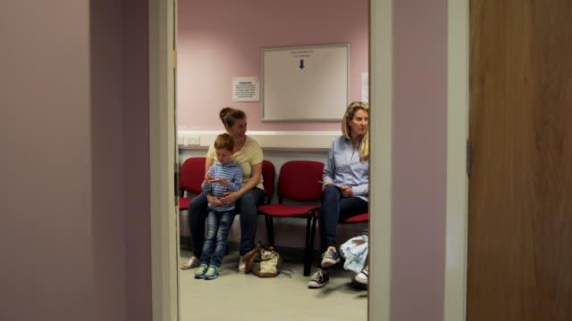 tittar genom dörren av en läkares väntrum - väntrum bildbanksvideor och videomaterial från bakom kulisserna