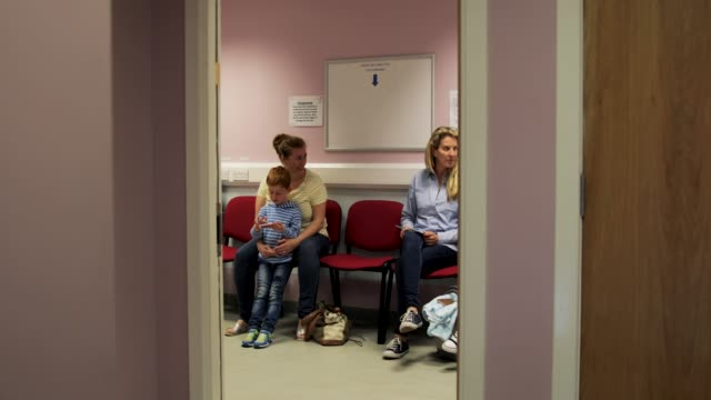 looking through the door of a doctor's waiting room - sala d'attesa video stock e b–roll