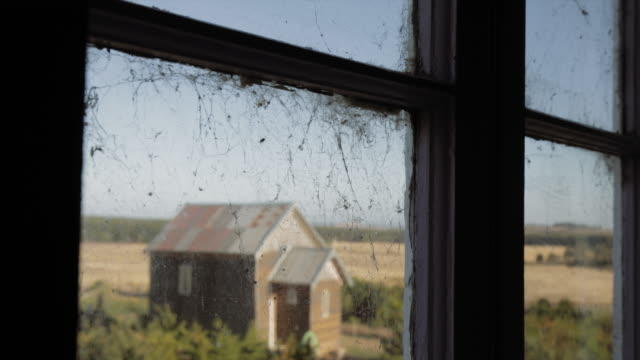 Looking through the window: a small church in a farm and a spider web, Victoria. Australia