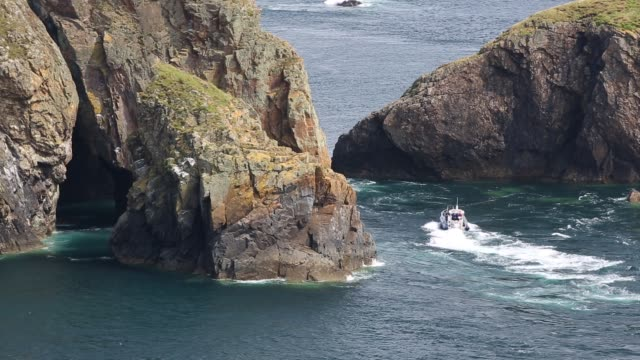 looking towards yns cantwr off the southern tip of ramsey island, pembrokeshire, wales, uk, with a tourist boat entering a sea cave. - ausflugsboot stock-videos und b-roll-filmmaterial