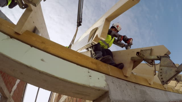 looking up at a builder attaching a beam on the roof of the house - roof beam stock videos & royalty-free footage