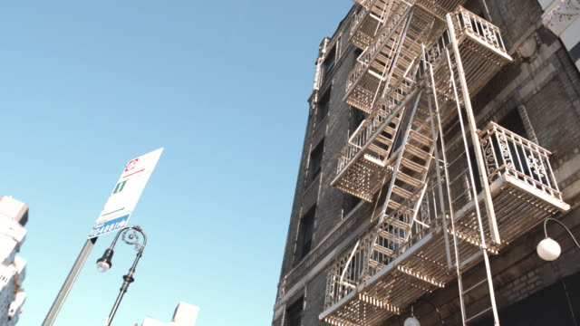 looking up at a fire escape on a new york city apartment building - fire escape stock videos & royalty-free footage