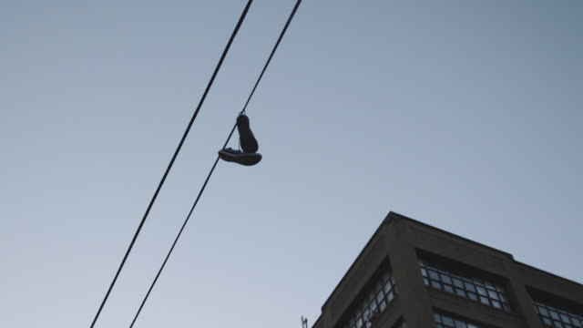 looking up at a pair of sneakers hanging on a telephone line in brooklyn - telephone line stock videos and b-roll footage