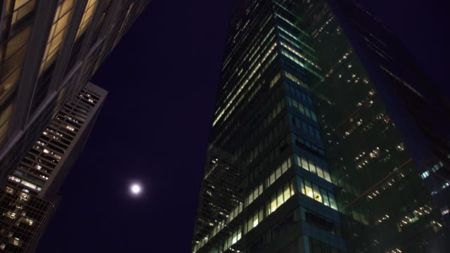looking up at full moon and towering skyscrapers at night - directly below stock videos & royalty-free footage