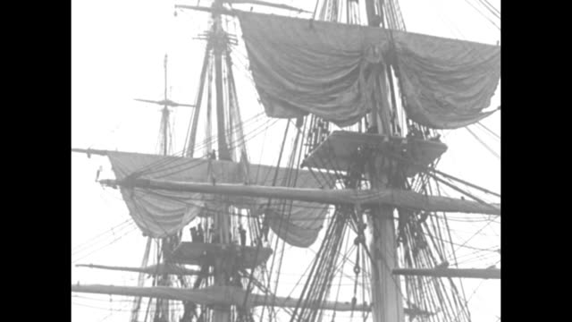 vídeos de stock e filmes b-roll de looking up at mast on board the uss constitution as crewmen wave and begin unfurling topsail / bow of constitution of in left foreground, as us navy... - embarcação comercial
