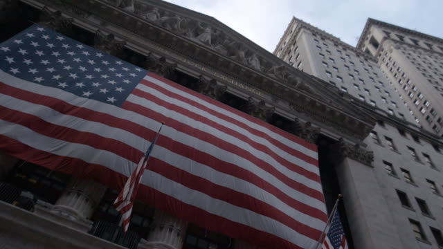 vídeos de stock, filmes e b-roll de looking up at the american flag hanging above new york city's wall street - cultura americana