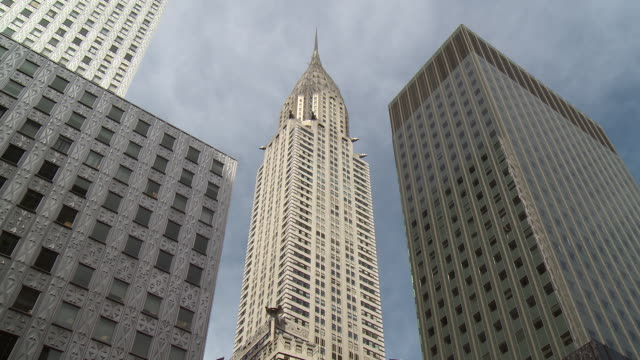 looking up at the chrysler building in manhattan.  other skyscrapers surround. - chrysler building stock-videos und b-roll-filmmaterial