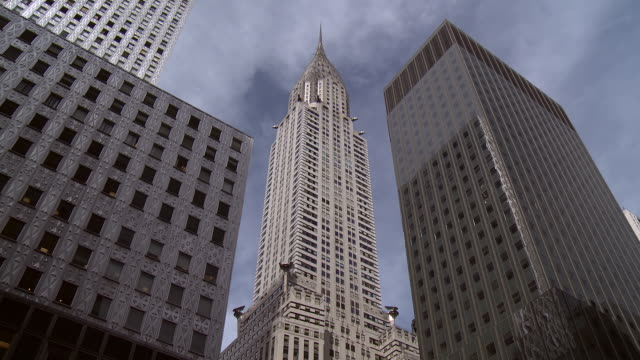 looking up at the chrysler building in manhattan.  other skyscrapers surround. - chrysler building stock videos & royalty-free footage