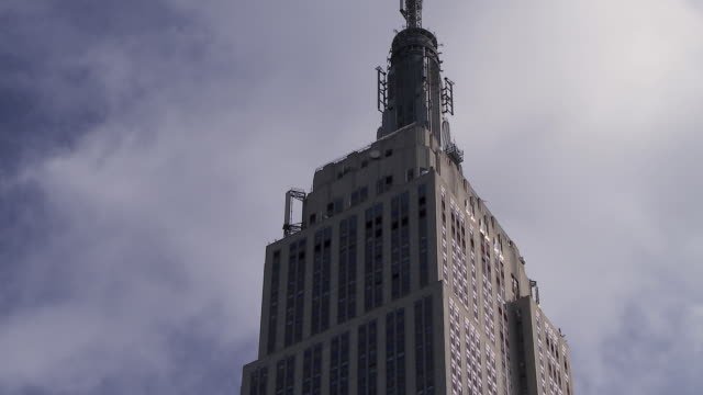 cu looking up at the tower of the empire states building in new york on a cloudy day. - empire state building stock-videos und b-roll-filmmaterial