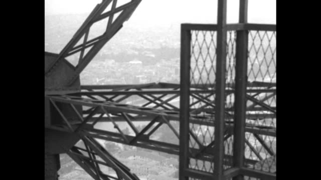 looking up exterior of eiffel tower / elevator moves up elevator shaft toward camera / vs as elevator goes up tower / cameraman and man carrying... - eiffel tower paris stock videos & royalty-free footage