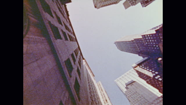 looking up from the ground at looming skyscrapers as they slowly spin - 1973年点の映像素材/bロール