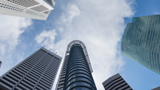 looking up on modern building with moving cloud and blue sky, direct below shot time lapse video - singapore stock videos & royalty-free footage