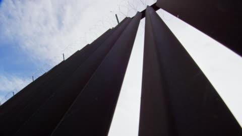 vídeos y material grabado en eventos de stock de mirando hacia arriba disparo de sol asomando a través de la pared fronteriza de acero-lat (en el lado de estados unidos) entre méxico y los estados unidos con razor wire en la parte superior en un día parcialmente nublado - cruzar