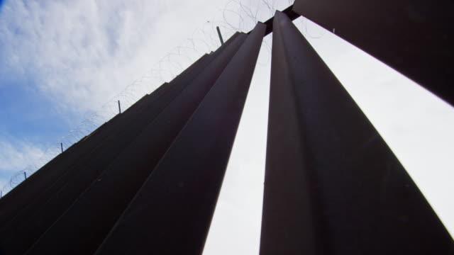 vídeos de stock, filmes e b-roll de looking up shot of sun peeking through the steel-slat border wall (do lado dos eua) entre o méxico e os estados unidos com arame farpado no topo em um dia parcialmente nublado - cruzar